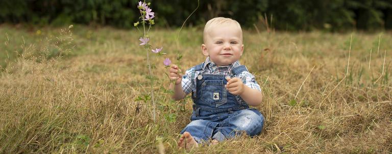 boy in blue sat in the long grass